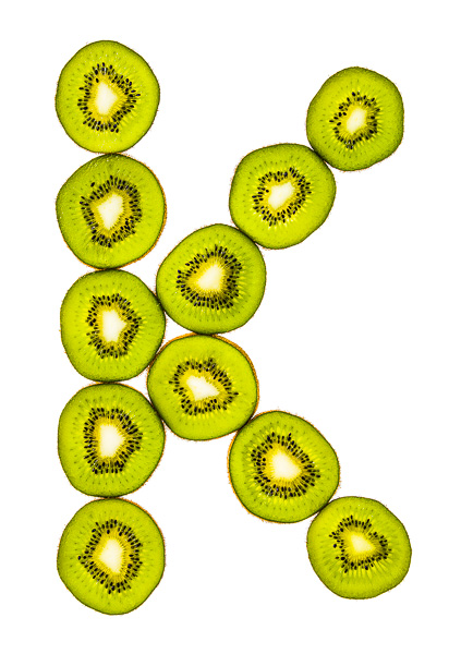 """Photo of sliced Kiwi Fruit, laid out in the shape of the letter """"K"""""""