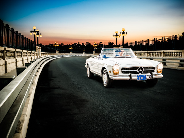 Photograph of a 1969 Mercedes Benz 280 SL driving across the Colorado Street Bridge at dusk.