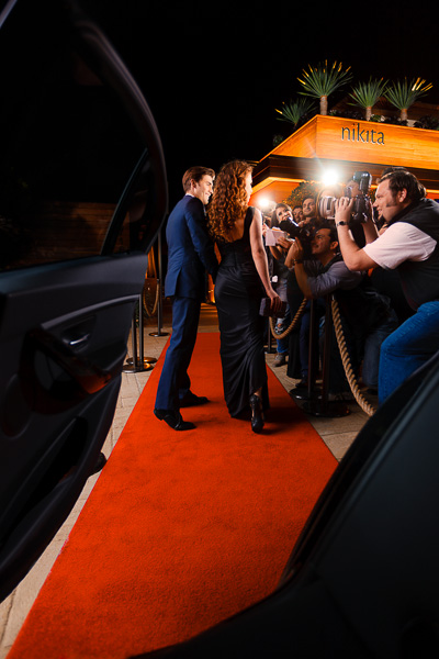 Photo of celebrities exiting car onto a red carpet with paparazzi and fans at a rope line.
