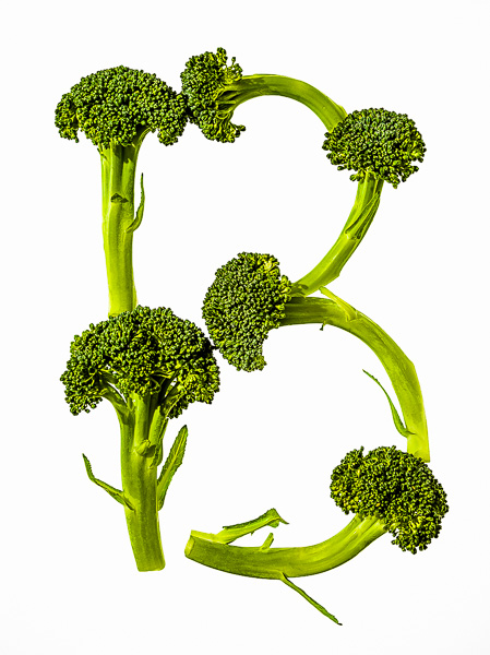 "Photo of Broccoli laid out in the shape of the letter ""B"""
