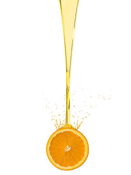 Photograph of orange oil pouring onto an orange slice.