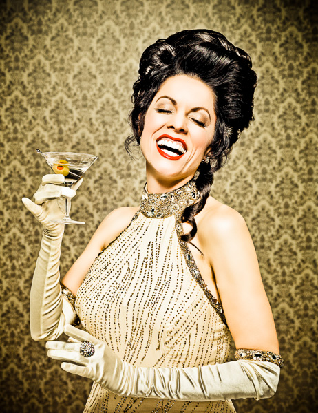 Photograph of a woman in 1940's attire holding a martini and throwing her head back in laughter.