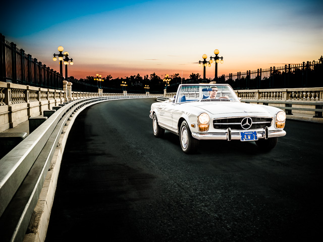 Photograph of a Mercedes Benz 280SL Convertible driving across the Colorado Street Bridge in Pasadena CA at sunset.