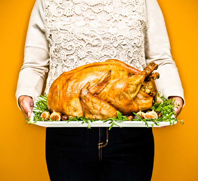 Photo of a woman holding a platter with a perfectly prepared turkey on it.