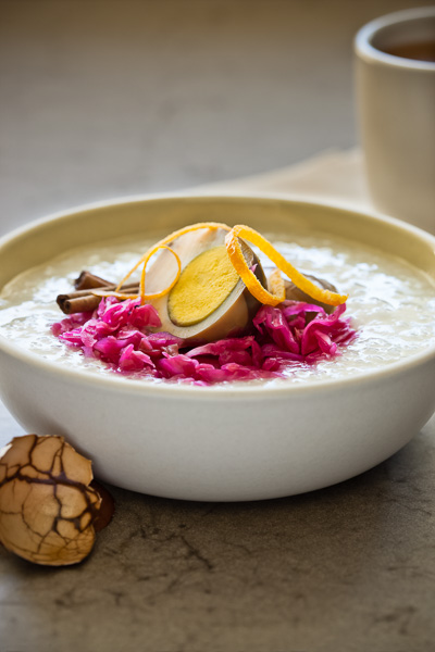 Photo of a bowl of Congee with Tea Eggs and Red Sauerkraut