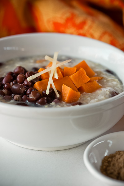 Photo of a bowl of congee with carrots beans and ginger on top.