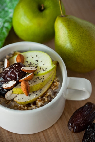 Photograph of Oatmeal in a cup with apples, pears, nuts and dates sprinkled on top.