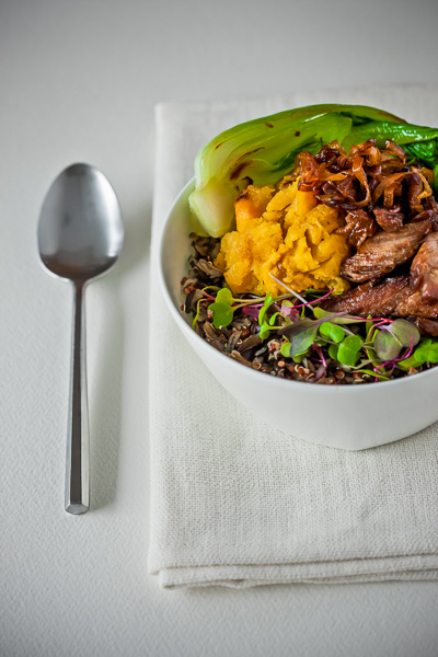 Photo of a rice bowl with chicken meat and vegetables on top.