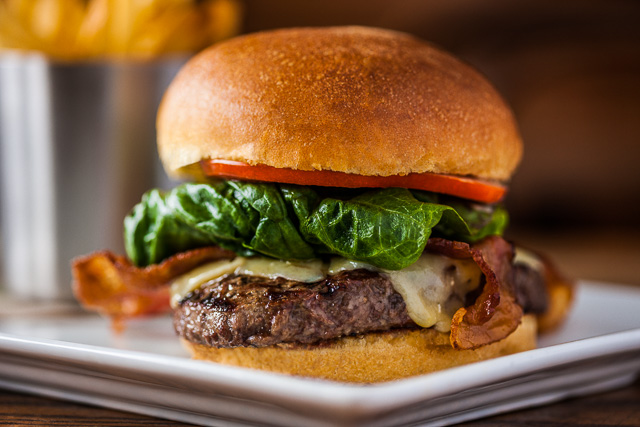 Photograph of a Juicy Hamburger with french fries in the background.
