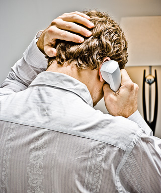 Photo of a man on the phone, shot from behind grabbing his head in frustration.