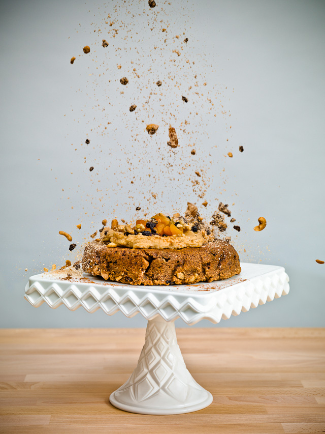 Photo of a cake on a platter with ingredients raining down on it.