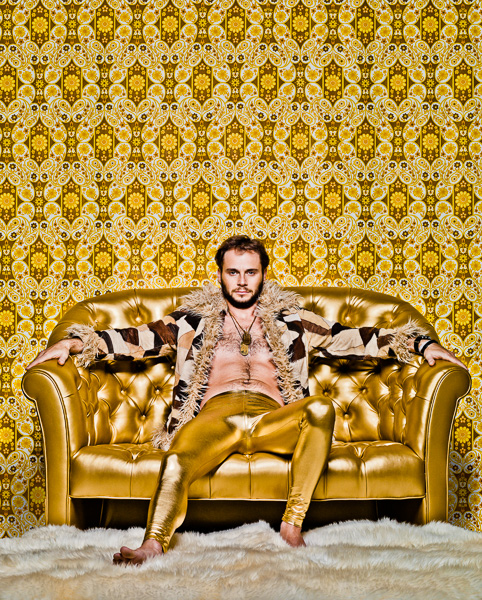 Photo of Jamesen Re dressed in Gold sitting on a Golden Couch
