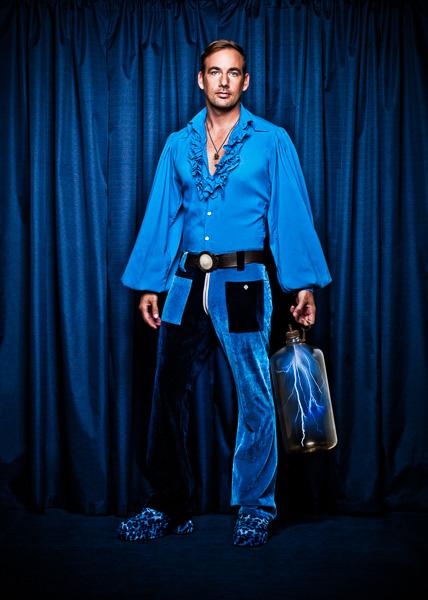 Photo of Dede Flemming dressed in Blue, holding a bottle with lightning inside