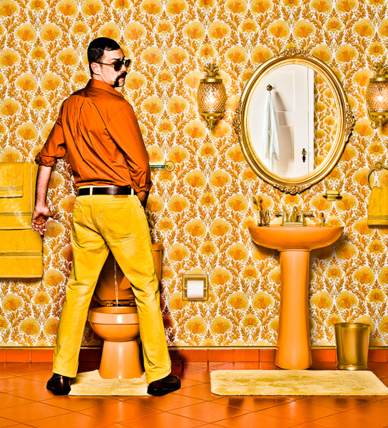 Photograph of a man in a 1970's decorated bathroom with gaudy wallpaper and orange and gold accents standing in front of a toilet peeing with cigarette in hand.