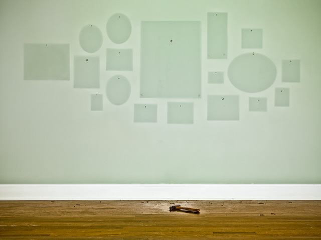 Photograph of an empty wall where photos use to hang showing that the paint has faded over time.