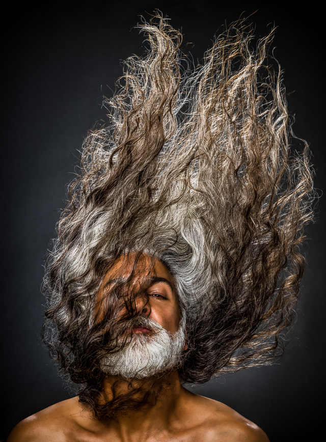 Portrait of a man with very long hair flipping it up over his head. © Dana Hursey Photography